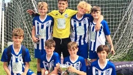 Ottery St Mary U12s with the Broadclyst FC Tournament troph. Picture CONTRIBUTED