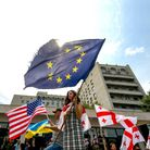 Protestors demanding political reform wave EU, Georgia and US flags during a rally in Tbilisi. Pictu