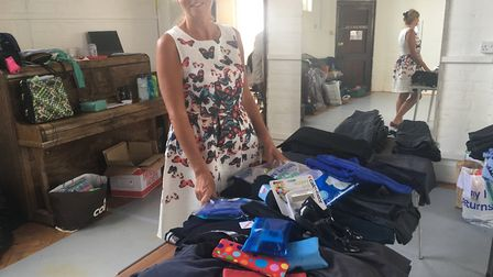 Andie Milne of Sid Valley Food Bank with the clothes and accessories donated to the uniform bank. Pi