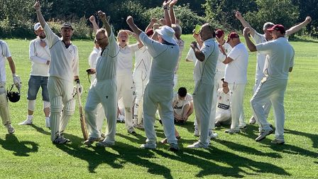 Tipton cricket players celebrarte after listening to radio commentary, during a 12 minute drinks bre