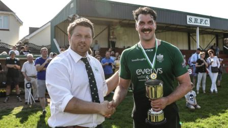 Sidmouth captain Ollie Pyne receiving the Devon Intermediate Cup from Glenn Channing, representing t
