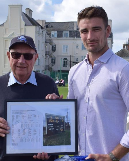 Mike Coxhead hands over a framed memento of the game against Dorset in which Josh Bess scored 203 an