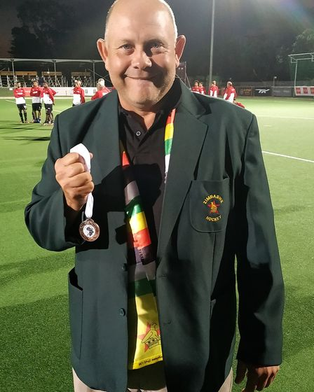Gus McVey with the bronze medal he and his Zimbabwe ladies team won at the Africa Olympic Qualifying