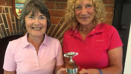 Sidmouth GolfG Club lady captain ill Paddon (left) receiving the Captain v Secretary Cup from the la