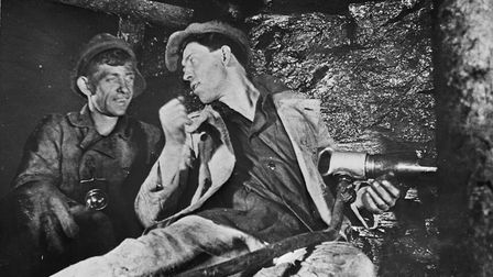 Alexey Stakhanov (right) explains his system to a fellow miner in the USSR between 1935 and 1945. Pi