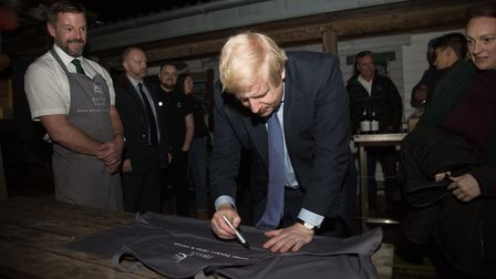 Prime Minister Boris Johnson signs an apron during his visit to Darts Farm. Ref exe 48 19TI 0377. Pi