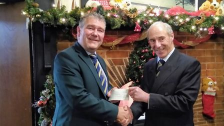 Sidmouth Golf Club captain Neil Holland is presented with a cheque of £1,000 towards his charity, Ca