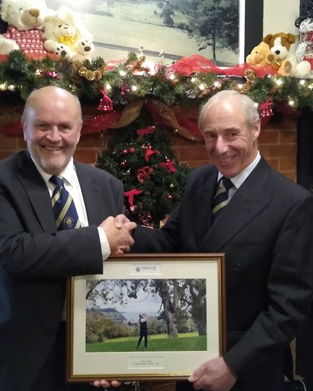 Sidmouth Golf Club's incoming seniors captain Mike Davis presents outgoing captain Chris Grubb with