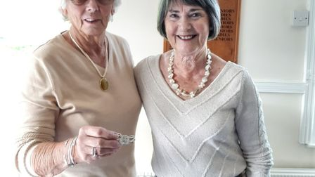 Sidmouth ladies captain Penny Lyne receiving the brooch of office from her predecessor Gill Paddon