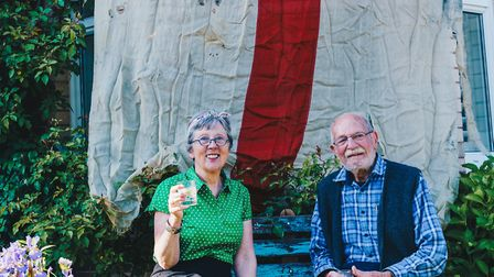 John and Lizzie Moore with his wartime White Ensign flag. Picture: Sarah Hall Photography