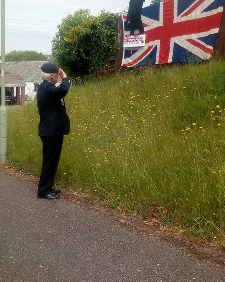 Ralph Hickman of the Sidmouth Royal British Legion salutes the flag in remembrance of VE Day Picture
