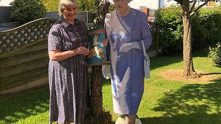 Norma Hoare in her Sidmouth garden with her scrapbook and 'The Queen'. Picture: Marian Wale