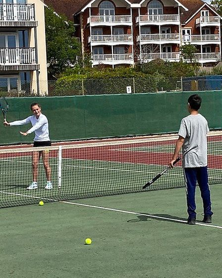 Sidmouth Tennis Club assistant coach Katie Wiltshire working with a junior member.