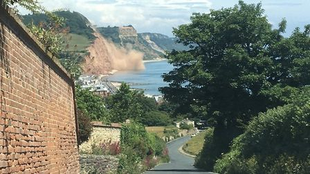 A cloud of dust rises as part of the cliff collapses. Picture: Kate Hudson