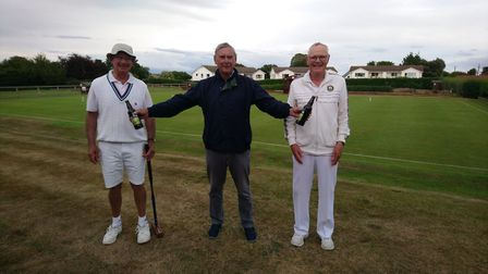 Peter Nelson (centre) presenting the bottles of beer to the winners of the consolation competition,