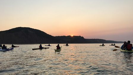 The Sidmouth Gig Club flotilla watches the sun come up over the cliffs at Branscombe. Picture; SGC