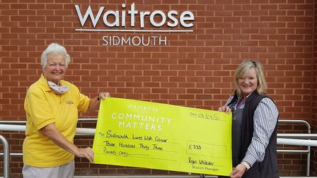 Kath Davies, president of the Sidmouth Living With Cancer Group, receives the cheque from Julie Mari