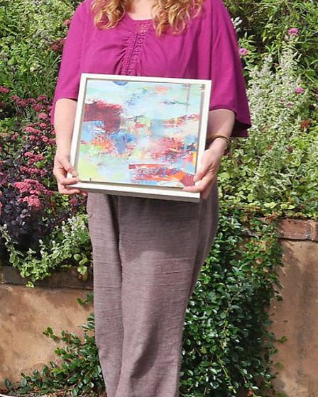 Lisa Parkyn displaying one of her abstract paintings