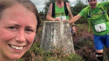 Sidmouth Running Club members Bex McDonald (left) Allen Kay proping up the trig point and the number 0ne Adrian Horne.