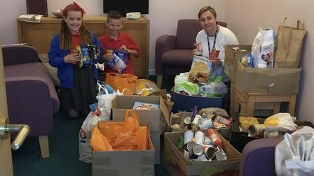 Rachel Clark with James and Emily from year five, sorting the donations ready to send to Weston Food