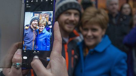 SNP leader Nicola Sturgeon takes pictures with supporters during a visit to Craig Boyd Hairdressing