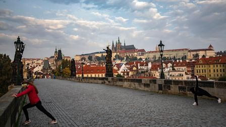 Two women stretch after a morning run on Prague's Charles Bridge, during the Czech Republic's partial coronavirus lockdown