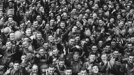 A large crowd of young English soldiers cheering as they wait to leave for France during the Second World War