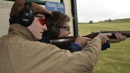 Olympic gold medallist Peter Wilson instructs first-time shot Rob Scammell, aged 14. Picture credit: