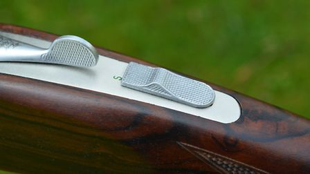 The safety and combined barrel selector are mounted conventionally on the top strap