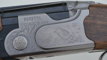 Game scene engravings decorate the silver-finished action