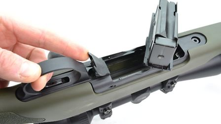 The magazine latch hides the rear action screw complicating disassembly