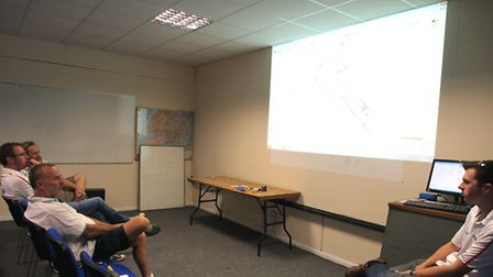 Weather reports and routes are examined at the briefing