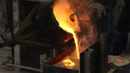 Pouring bronze into a mould at the foundry at Vrchlabi, Czech Republic
