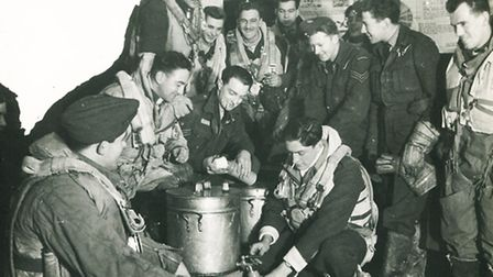 Rusty (centre, taking the top off his flask) with fellow crewmen at Ludford Magna in 1944. Note the