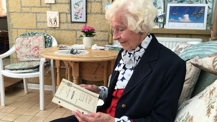 Mary at home holding the ATA notes for the Mosquito. Seconded to the RAF after leaving the ATA she a