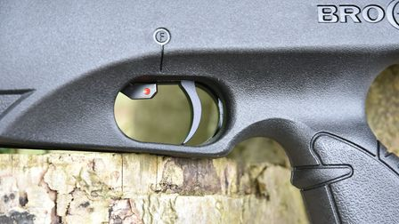 The safety sits right in front of the trigger blade