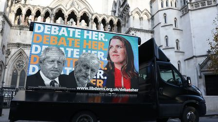 An advertising van showing Prime Minister Boris Johnson, Labour Party leader Jeremy Corbyn and Liber
