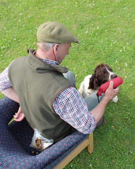 ... bring the dummy out from behind you and present it to the dog. He will instinctively touch it wi