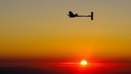 """Experimental aircraft """"Solar Impulse"""" with pilot Andre Borschberg onboard flyes at sunrise above Pay"""