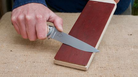 Drawing the sharpened blade toward the body on a home made leather strop to remove the burr