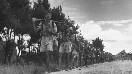 Chinese foot soldiers, wearing straw sandals, marching along a road