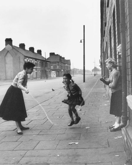 Shirley Bassey joins in a skipping game with members of her family outside their home in the Tiger Bay area of Cardiff, in...