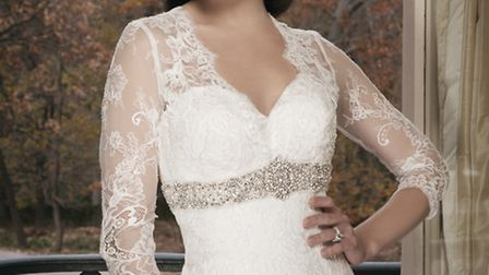 An all over lace fit and flare gown featuring three-quarter length sleeves by Justin Alexander. The