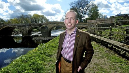 Cllr Richard Sweetring in front of the still-closed bridge in Tadcaster
