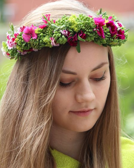 A festival flower crown made from florets of Angelica and bold pink Dianthus
