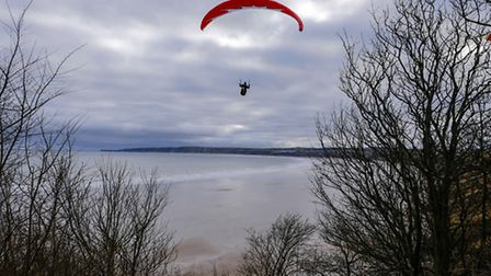A paraglider flies silently across Filey Bay