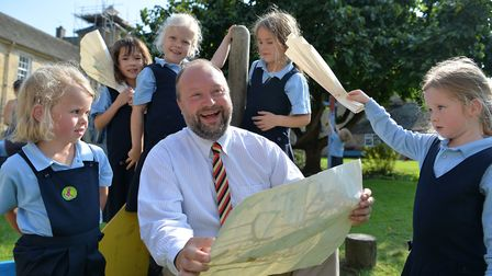 Dr David Moses has fun with some of the younger members of his independent Catholic school