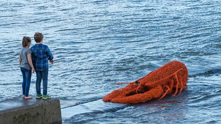 Children on the harbour wall near a sculpture of a giant lobster created by Emma Stothard for an ear