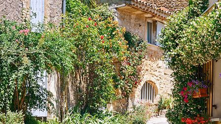 Stone houses among beautiful flowers in Provencal village. (c) irakite