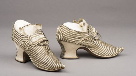 A pair of ivory white satin shoes with curved toes and Louis heels (circa 1730)